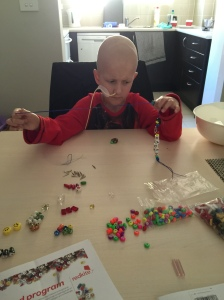 Kaden having a go at putting the beads on the necklace, getting frustrated until we worked out there was an easier way.